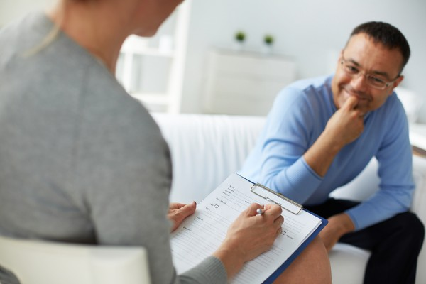 Female psychologist consulting mature man during psychological t